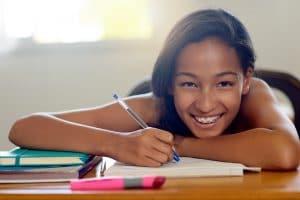 Portrait of a young schoolgirl doing her homework in class